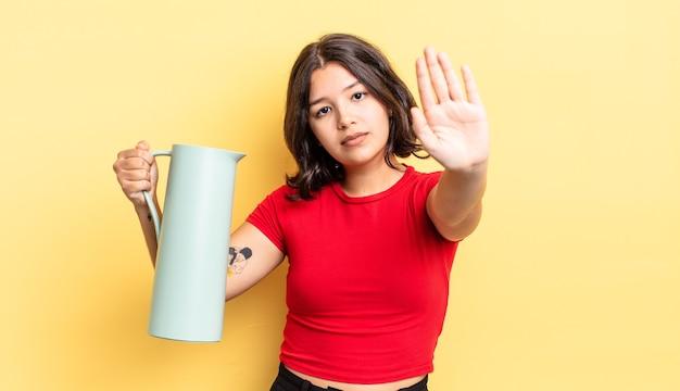 Młoda kobieta hiszpanin patrząc poważne pokazując otwartą dłoń co gest zatrzymania. koncepcja termosu