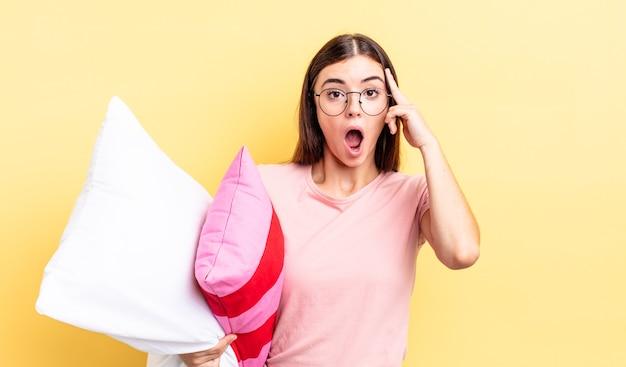 Młoda kobieta hiszpanin patrząc zaskoczony, realizując nową myśl, pomysł lub koncepcję. koncepcja piżamy i poduszki