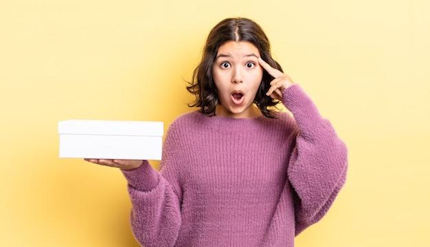 Młoda kobieta hiszpanin patrząc zaskoczony, realizując nową myśl, pomysł lub koncepcję. koncepcja pustego pudełka