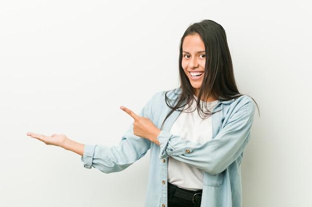 Młoda kobieta hiszpanin podekscytowany, trzymając kopię miejsca na dłoni.