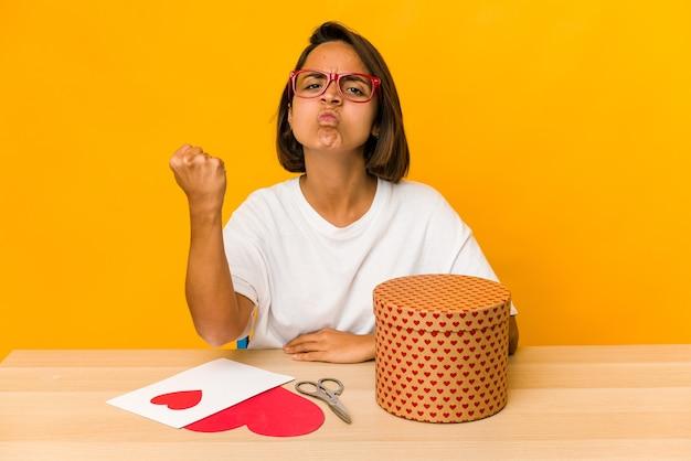 Młoda kobieta hiszpanin przygotowuje prezent valentine na białym tle pokazując pięść do aparatu, agresywny wyraz twarzy.