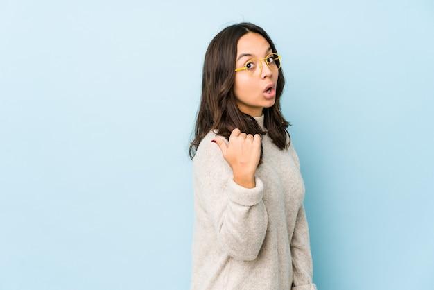 Młoda kobieta hiszpanin rasy mieszanej izolowane punkty z kciukiem z dala, śmiejąc się i beztrosko.