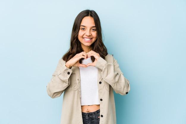 Młoda kobieta hiszpanin rasy mieszanej izolowane uśmiechając się i pokazując kształt serca rękami.