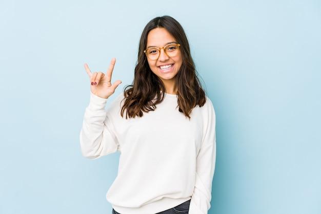 Młoda kobieta hiszpanin rasy mieszanej na białym tle przedstawiający gest rogów jako koncepcja rewolucji.