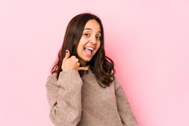 Młoda kobieta hiszpanin rasy mieszanej na białym tle przedstawiający gest rozmowy telefonicznej palcami.