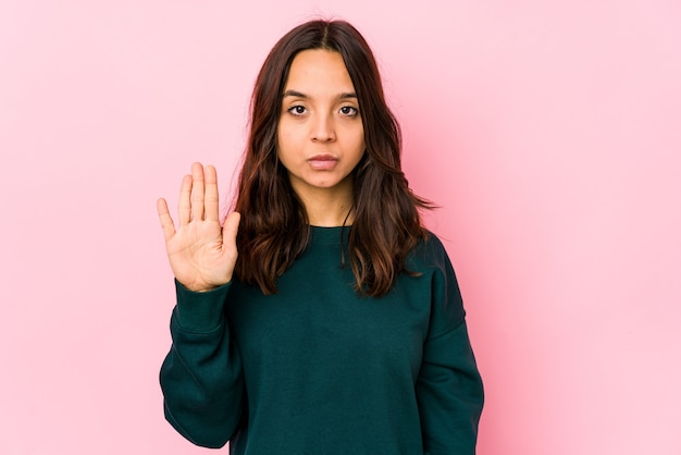 Młoda kobieta hiszpanin rasy mieszanej na białym tle stojący z wyciągniętą ręką pokazujący znak stopu, uniemożliwiając ci.