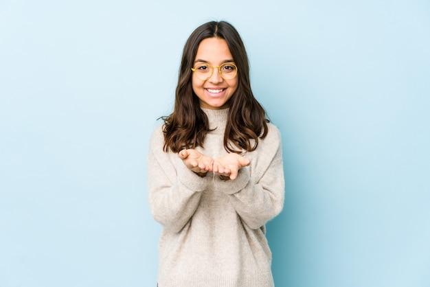 Młoda kobieta hiszpanin rasy mieszanej na białym tle trzyma coś z palmami, oferując do kamery.