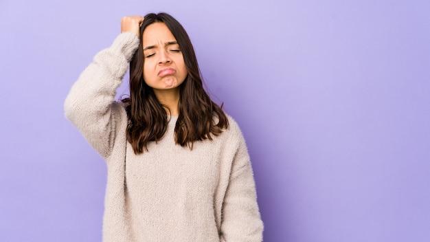 Młoda kobieta hiszpanin rasy mieszanej na białym tle zmęczony i bardzo senny, trzymając rękę na głowie.