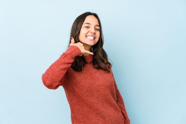 Młoda kobieta hiszpanin rasy mieszanej pokazano gest rozmowy telefonicznej palcami.
