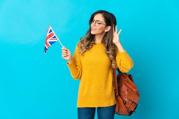 Młoda kobieta hiszpanin trzyma flagę zjednoczonego królestwa na białym tle na niebieskiej przestrzeni, słuchając czegoś, kładąc rękę na uchu