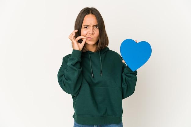 Młoda kobieta hiszpanin trzyma kształt serca z palcami na ustach, zachowując tajemnicę.