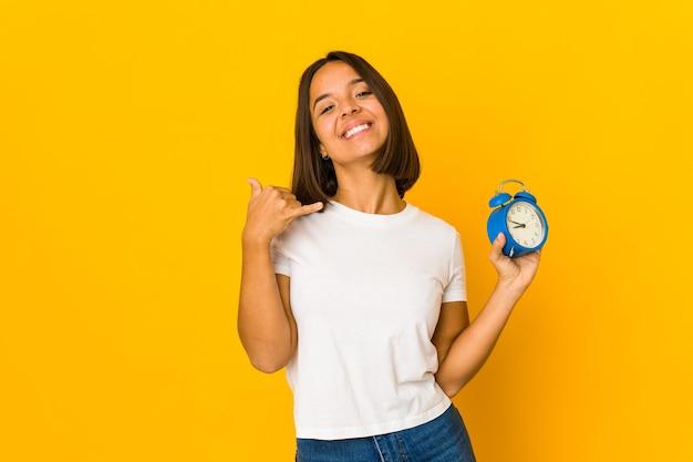 Młoda kobieta hiszpanin trzyma megafon przedstawiający gest rozmowy telefonicznej palcami.