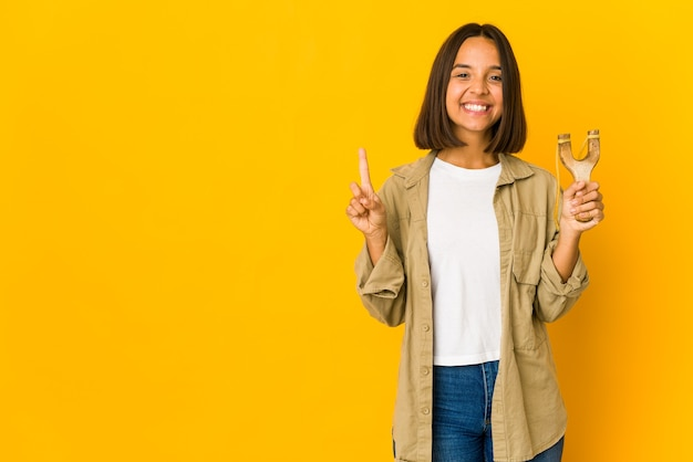Młoda kobieta hiszpanin trzyma procę pokazując numer jeden z palcem.