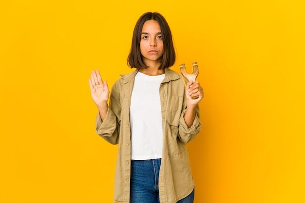 Młoda kobieta hiszpanin trzyma procę stojącą z wyciągniętą ręką pokazujący znak stopu, uniemożliwiając ci.