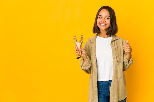Młoda kobieta hiszpanin trzyma procę uśmiechając się i podnosząc kciuk do góry