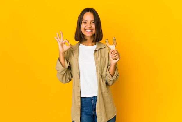 Młoda kobieta hiszpanin trzyma procę wesoły i pewny siebie, pokazując ok gest.