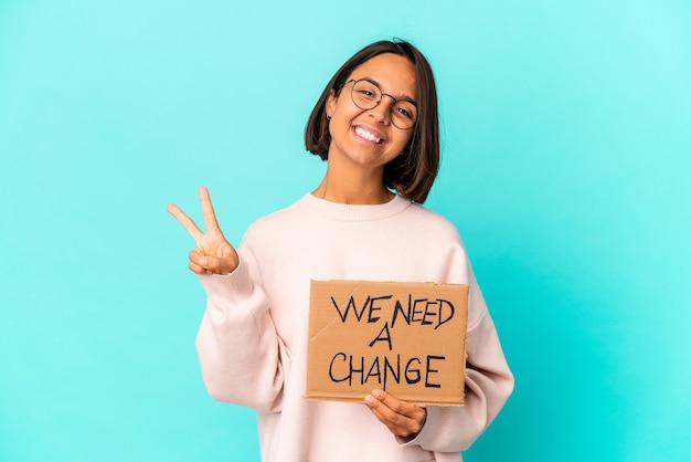 Młoda kobieta hiszpanin trzymająca inspirującą wiadomość o zmianie na tekturze przedstawiająca numer dwa palcami