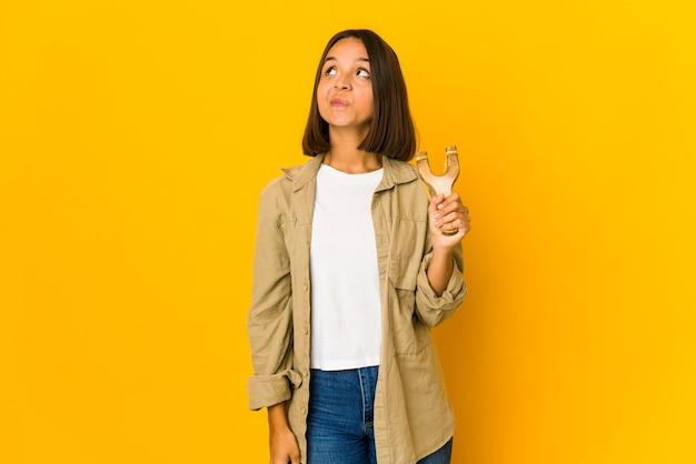 Młoda kobieta hiszpanin trzymająca procę marzy o osiągnięciu celów i zamierzeń