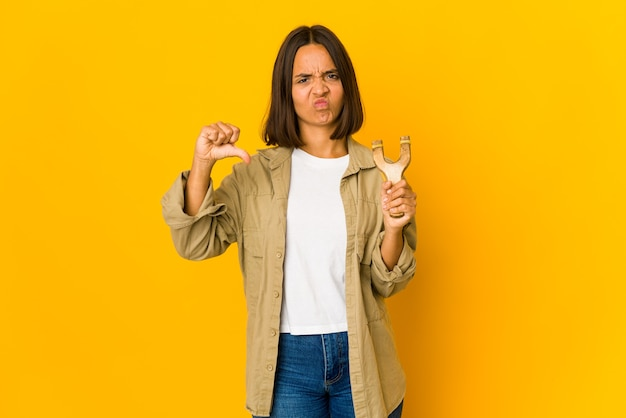 Młoda kobieta hiszpanin trzymająca procę pokazującą gest niechęci, kciuki w dół. pojęcie sporu.
