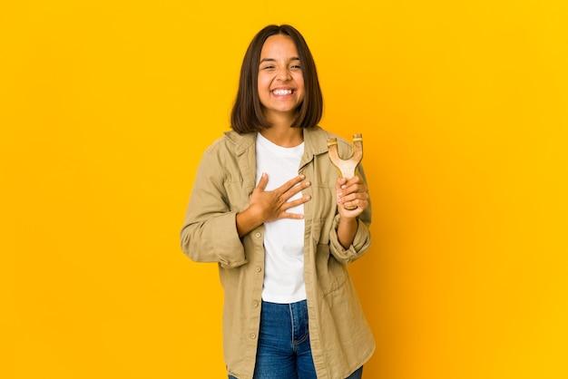 Młoda kobieta hiszpanin trzymająca procę śmieje się głośno trzymając rękę na piersi.