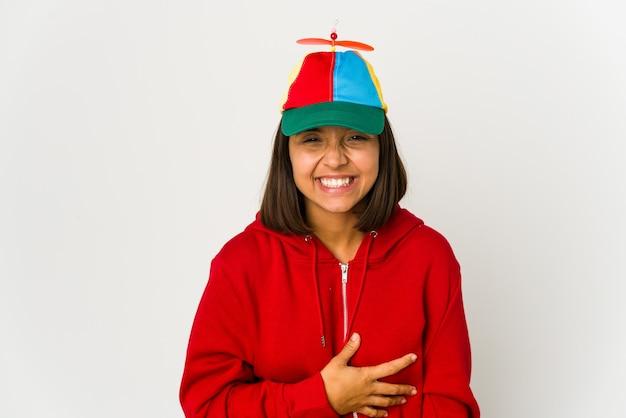 Młoda kobieta hiszpanin ubrana w czapkę ze śmigłem na białym tle śmiechu i zabawy.