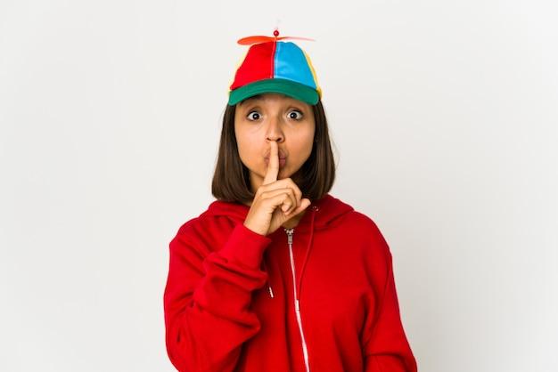 Młoda kobieta hiszpanin ubrana w czapkę ze śmigłem na białym tle, zachowując tajemnicę lub prosząc o ciszę.