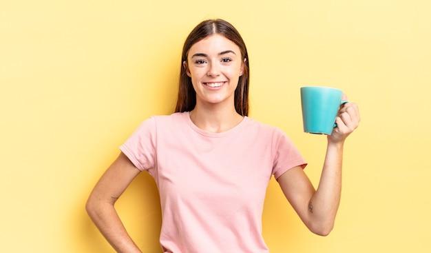 Młoda kobieta hiszpanin uśmiechający się szczęśliwie z ręką na biodrze i pewny siebie. koncepcja filiżanki kawy