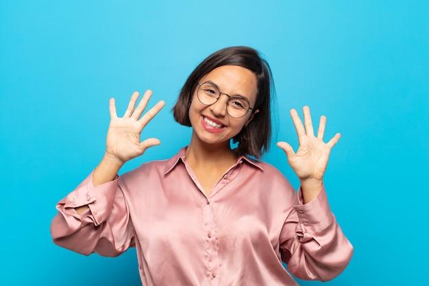 Młoda kobieta hiszpanin uśmiechnięta i przyjazna, pokazując numer dziesięć lub dziesiątą ręką do przodu
