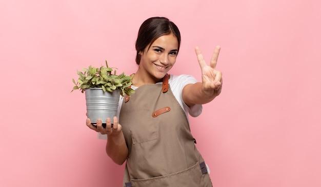 Młoda kobieta hiszpanin uśmiechnięta i wyglądająca przyjaźnie, pokazująca numer dwa lub sekundę z ręką do przodu, odliczanie