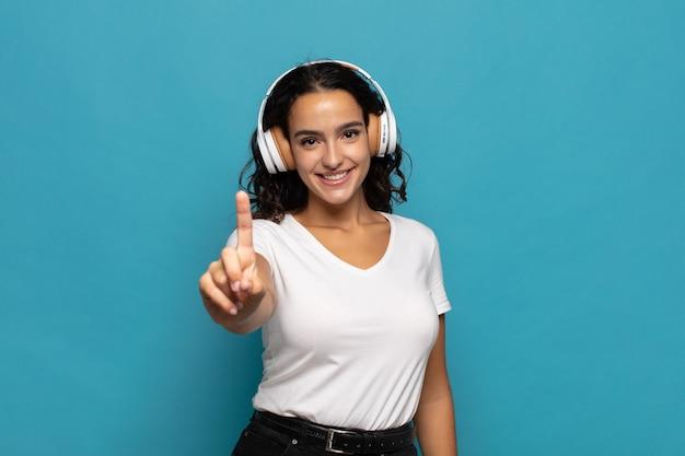 Młoda kobieta hiszpanin uśmiechnięta i wyglądająca przyjaźnie, pokazująca numer jeden lub pierwszy z ręką do przodu, odliczający w dół