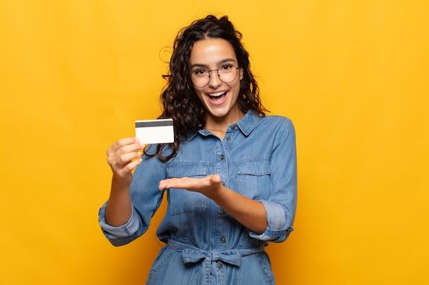 Młoda kobieta hiszpanin uśmiechnięty radośnie, czując się szczęśliwy i przedstawiający koncepcję w przestrzeni kopii z dłoni