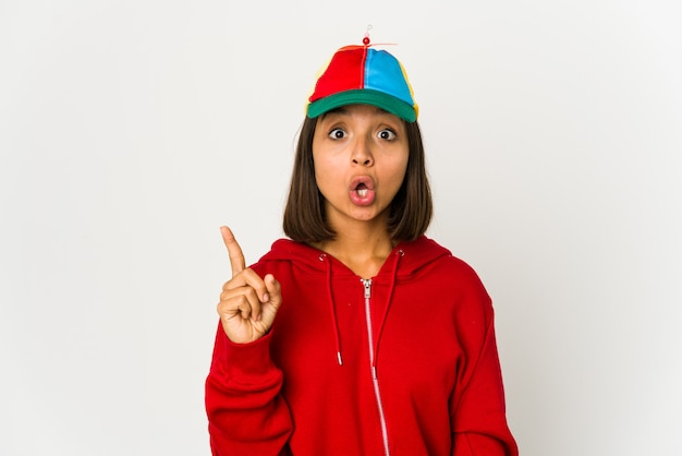 Młoda kobieta hiszpanin w czapce ze śmigłem na białym tle mając jakiś świetny pomysł, pojęcie kreatywności.