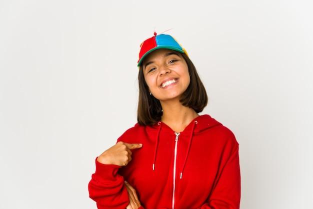 Młoda kobieta hiszpanin w czapce ze śmigłem na białym tle osoba wskazująca ręką na przestrzeni kopii koszuli, dumna i pewna siebie