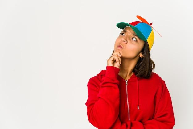 Młoda kobieta hiszpanin w czapce ze śmigłem na białym tle patrząc w bok z wyrazem wątpliwości i sceptycyzmu.