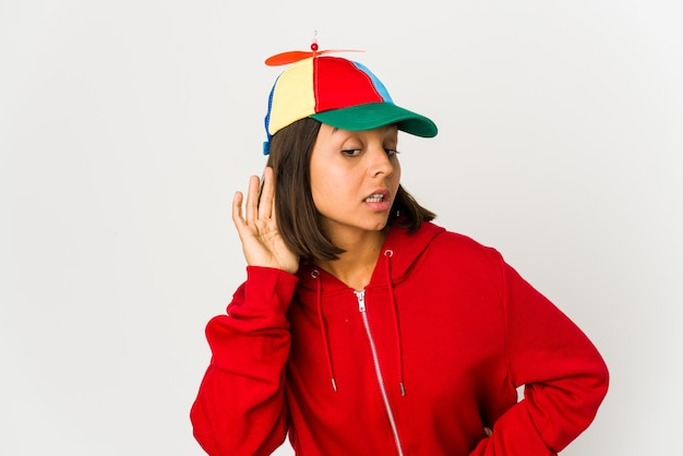 Młoda kobieta hiszpanin w czapce ze śmigłem na białym tle próbuje słuchać plotek.