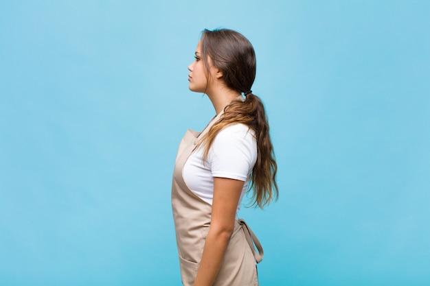 Młoda kobieta hiszpanin w widoku profilu chce skopiować przestrzeń do przodu, myśleć, wyobrażać sobie lub marzyć