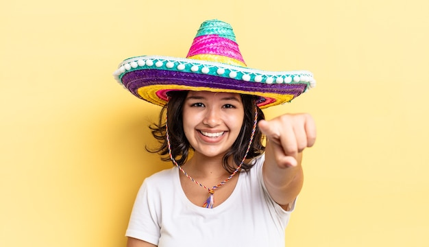 Młoda kobieta hiszpanin, wskazując na aparat wybierając ciebie. koncepcja meksykańskiego kapelusza