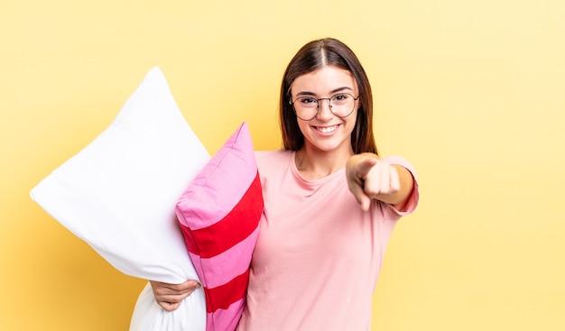 Młoda kobieta hiszpanin, wskazując na aparat wybierając ciebie. koncepcja piżamy i poduszki