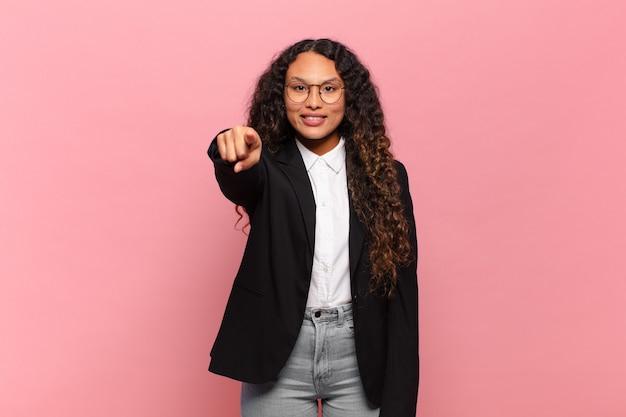 Młoda kobieta hiszpanin, wskazując na aparat z zadowolonym, pewnym siebie, przyjaznym uśmiechem, wybierając ciebie. pomysł na biznes