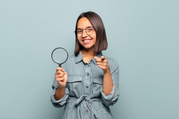 Młoda kobieta hiszpanin, wskazując na aparat z zadowolonym, pewnym siebie, przyjaznym uśmiechem, wybierając ciebie