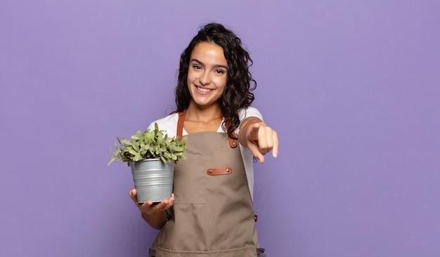 Młoda kobieta hiszpanin wskazująca na przód z zadowolonym, pewnym siebie, przyjaznym uśmiechem, wybiera ciebie