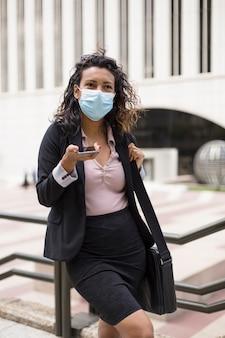 Młoda kobieta hiszpanin z maską na zewnątrz przy użyciu jej inteligentnego telefonu. osoba przedsiębiorcza. covid19.