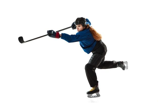 Młoda kobieta hokeista z kijem na lodzie i białej ścianie. sportsmenka na sobie sprzęt i szkolenie w kasku. pojęcie sportu, zdrowego stylu życia, ruchu, akcji, ludzkich emocji.