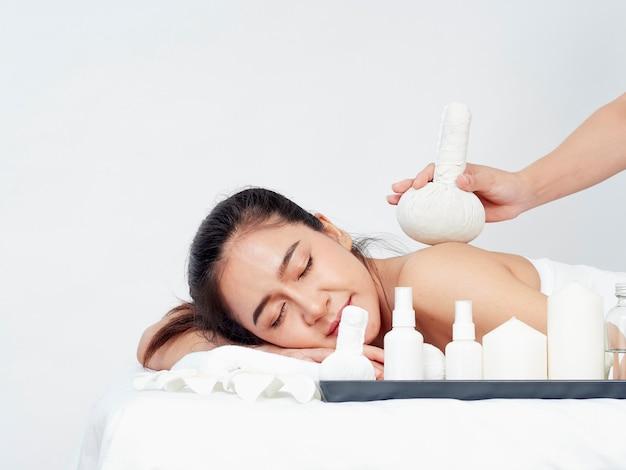 Młoda kobieta i akcesoria spa na stole do masażu