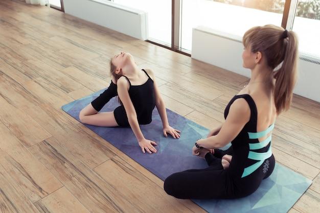 Młoda kobieta i córka robią ćwiczenia jogi