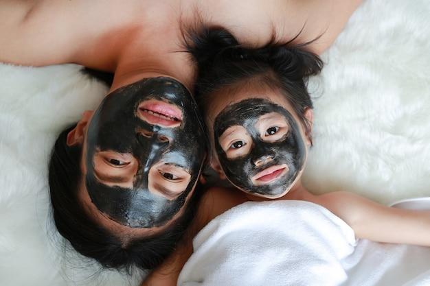 Młoda kobieta i dziecko dziewczyna w węglowej obieranie twarzy masce