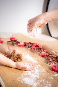 Młoda kobieta i dziecko szykując się do świąt bożego narodzenia. pieczenie ciasteczek imbirowych. posypanie mąką.