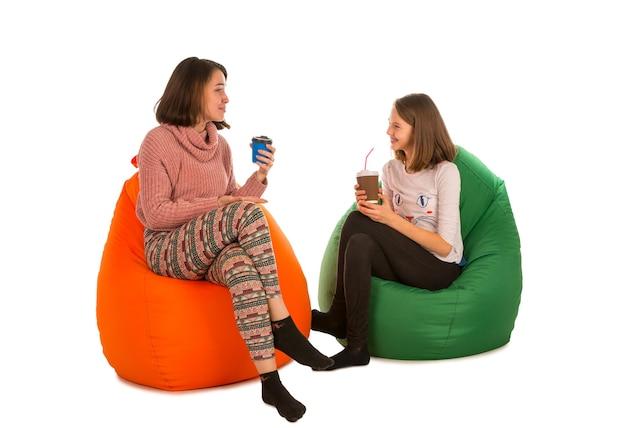 Młoda kobieta i dziewczyna siedzi na krzesłach beanbag i picia kawy na białym tle