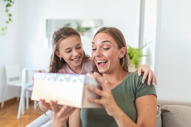 Młoda kobieta i dziewczyna w domu świętują dzień matki siedząc na kanapie córka przytulająca matka całująca policzek mama śmiejąca się radosna trzymająca pudełko