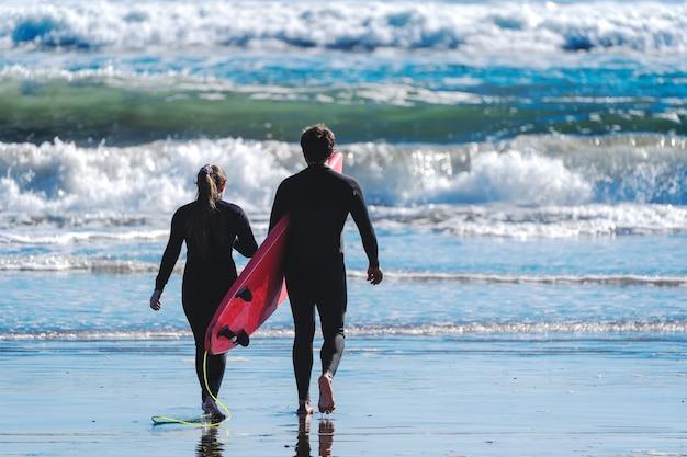 Młoda kobieta i instruktor surfingu wchodzą do wody, aby posurfować na falach
